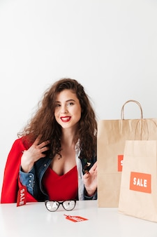 Sorrindo em compras menina bonita sentada com sacolas de papel