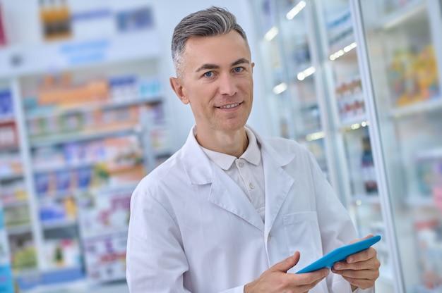 Sorrindo em jaleco médico com comprimido na farmácia