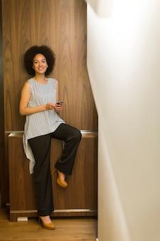 Sorrindo empresária afro-americana, usando telefone celular no escritório