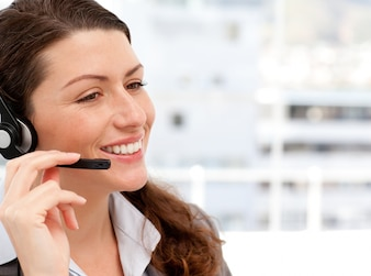 Sorrindo empresária falando ao telefone com fones de ouvido