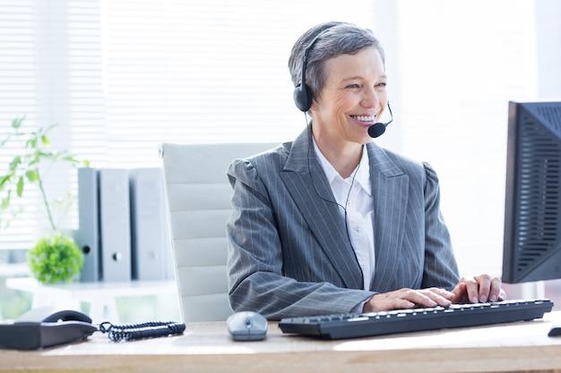 Sorrindo empresária usando computador e telefonando