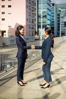 Sorrindo empresárias apertando as mãos