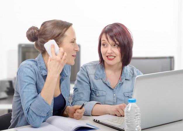 Sorrindo empresárias usando telefone celular no escritório