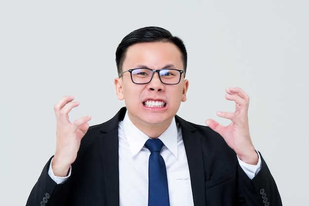 Sorrindo empresário asiático sentindo raiva com as mãos apertando