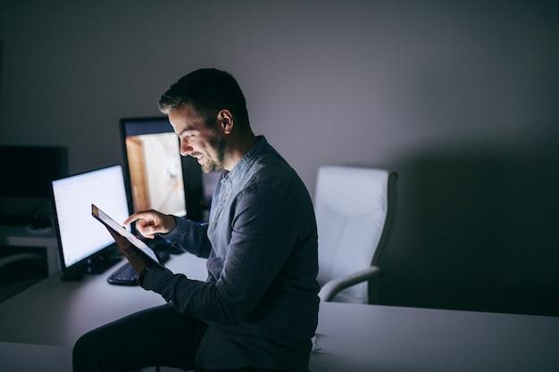 Sorrindo empresário barbudo caucasiano usando tablet enquanto está sentado na mesa no escritório tarde da noite.