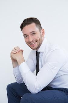 Sorrindo empresário bonito apoiado em joelhos