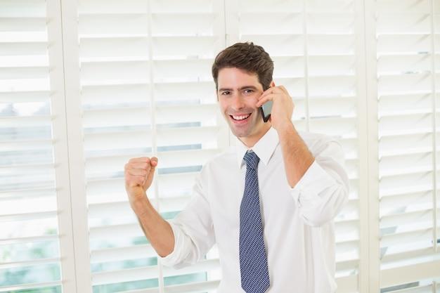 Sorrindo, empresário, usando, móvel, telefone, apertar, punho