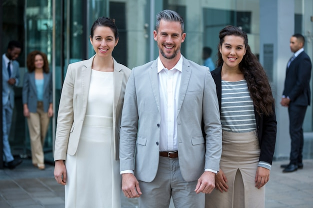 Sorrindo empresários de pé no prédio de escritórios