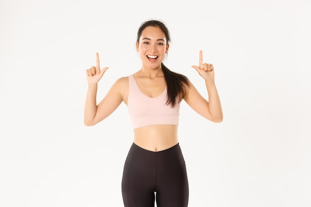 Sorrindo energizada menina asiática fitness, apontando o dedo para cima, seu logotipo banner.