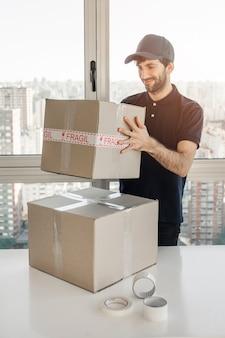 Sorrindo, entrega homem, segurando, pacote