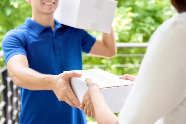 Sorrindo entregador de uniforme azul, entregando caixa de encomendas para uma mulher