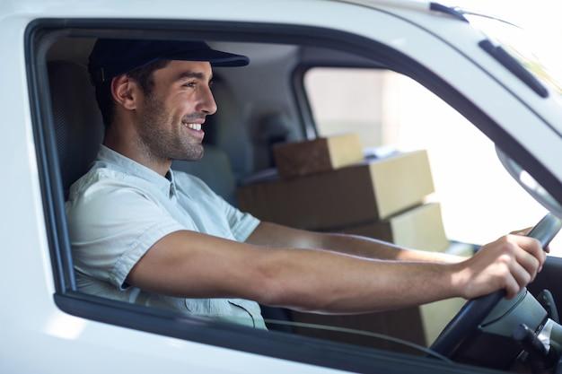 Sorrindo entregador dirigindo van