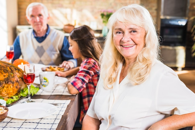Sorrindo, envelhecido, mulher senta-se mesa