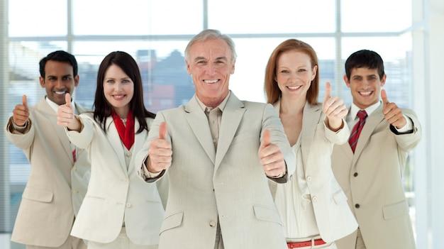 Sorrindo equipe de negócios multi-étnica com polegares para cima