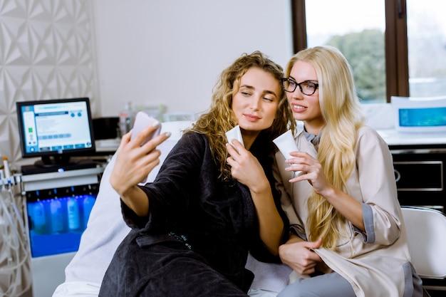 Sorrindo, esteticista de mulheres e paciente do sexo feminino com amostras de creme no salão de beleza, se divertindo enquanto tirava foto de selfie juntos após o procedimento.