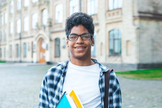 Sorrindo estudante afro-americano com óculos e com livros perto da faculdade. retrato de um jovem negro feliz em pé em uma universidade