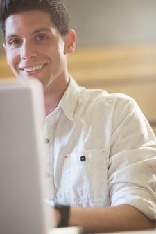 Sorrindo, estudante masculino, usando computador portátil, em, corredor leitura