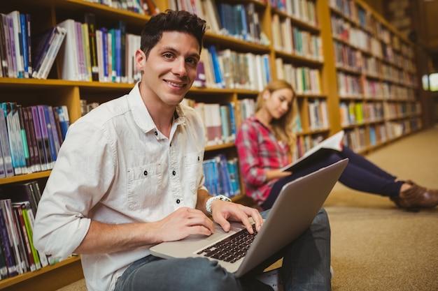 Sorrindo, estudante, usando computador portátil, ligado, chão, em, biblioteca