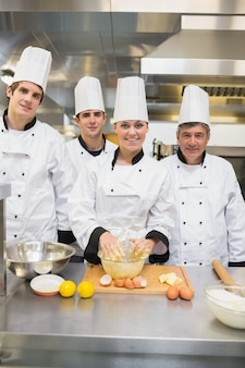 Sorrindo estudantes de culinária com professor de pastelaria