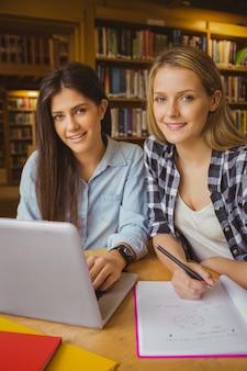 Sorrindo, estudantes, usando computador portátil, em, biblioteca