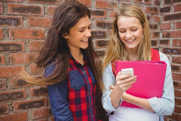 Sorrindo, estudantes, usando, smartphone, em, universidade