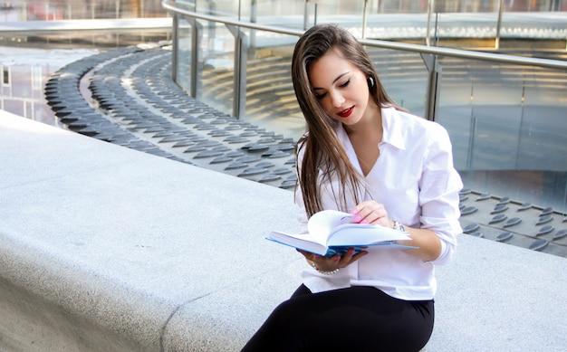 Sorrindo, executiva, lendo um livro