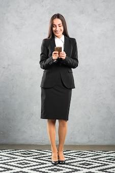 Sorrindo, executiva, mensagem texto, ligado, smartphone, contra, parede concreta