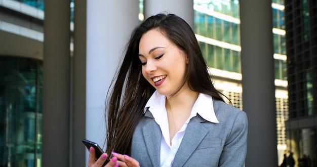 Sorrindo, executiva, usando, um, smartphone, ao ar livre