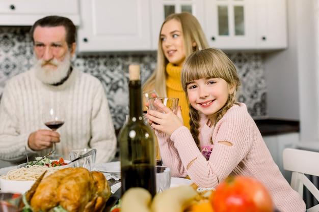 Sorrindo família jantando em casa, concentre-se na menina sorridente segurando copo com suco
