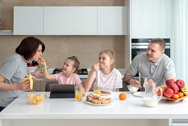 Sorrindo família jantar juntos na mesa da cozinha e se divertindo, pais com duas filhas