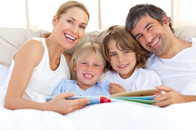 Sorrindo, família, lendo um livro, cama