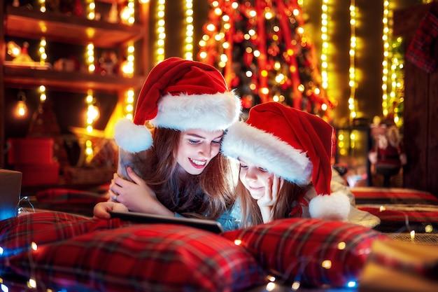 Sorrindo família mãe e filha em chapéus de papai noel e pijamas assistindo vídeo engraçado ou escolhendo presentes no tablet digital