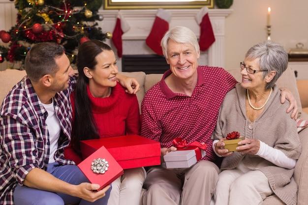 Sorrindo, família, segurando, presente, ligado, sofá