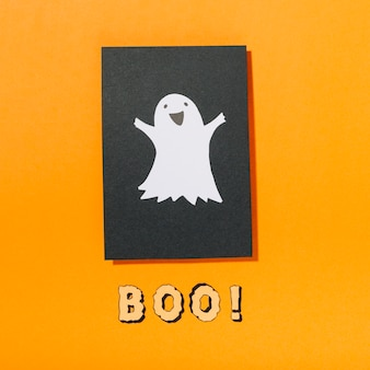 Sorrindo fantasma em pedaço de papel preto com boo! inscrição abaixo