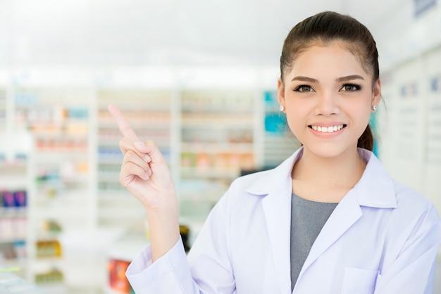 Sorrindo farmacêutico feminino asiático na farmácia ou farmácia, apontando o dedo no espaço vazio