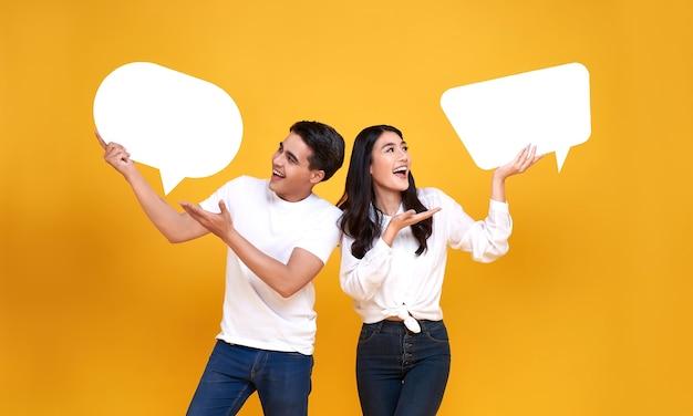 Sorrindo feliz casal asiático segurando balões de fala em branco em amarelo.