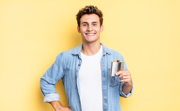 Sorrindo feliz com uma mão no quadril e atitude confiante, positiva, orgulhosa e amigável. conceito de frasco de álcool