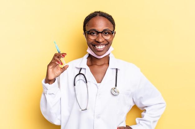 Sorrindo feliz com uma mão no quadril e atitude confiante, positiva, orgulhosa e amigável. conceito de médico e seringa