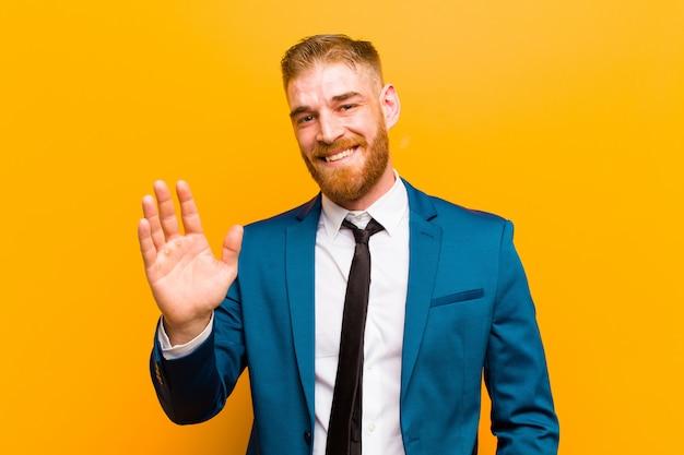 Sorrindo feliz e alegremente, acenando com a mão, dando as boas-vindas e cumprimentando-o ou dizendo adeus