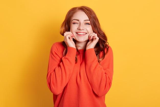 Sorrindo feliz e linda senhora beliscando suas bochechas