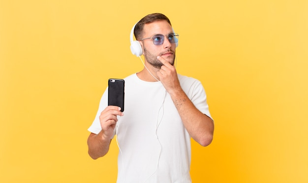 Sorrindo feliz e sonhando acordado ou duvidando, ouvindo música com fones de ouvido e um smartphone