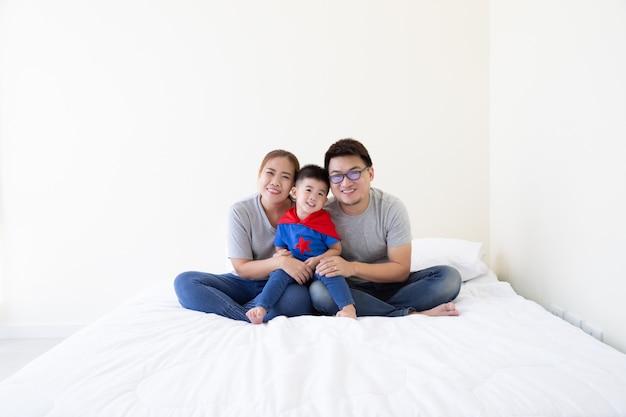 Sorrindo feliz família asiática e filho vestindo terno de super-herói sentado na cama branca no quarto