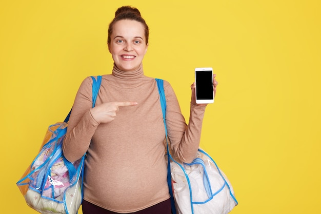Sorrindo feliz futura mãe segurando sacolas com coisas para dar à luz, posando contra uma parede amarela com o telefone nas mãos e apontando para uma tela em branco com o dedo indicador.