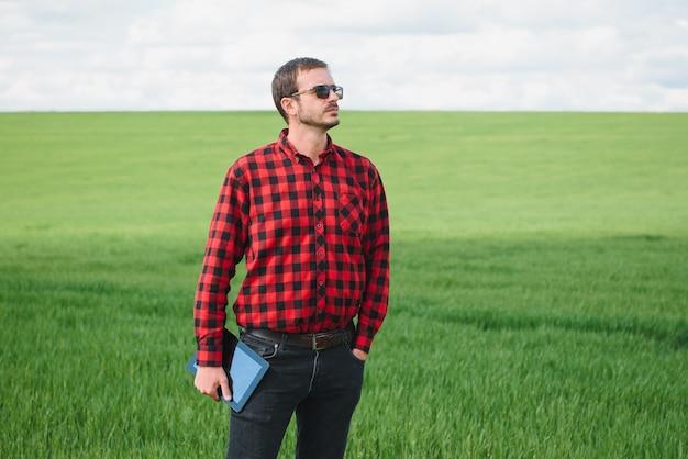 Sorrindo feliz jovem agricultor ou agrônomo usando um tablet em um campo de trigo. foto panorâmica de grande angular