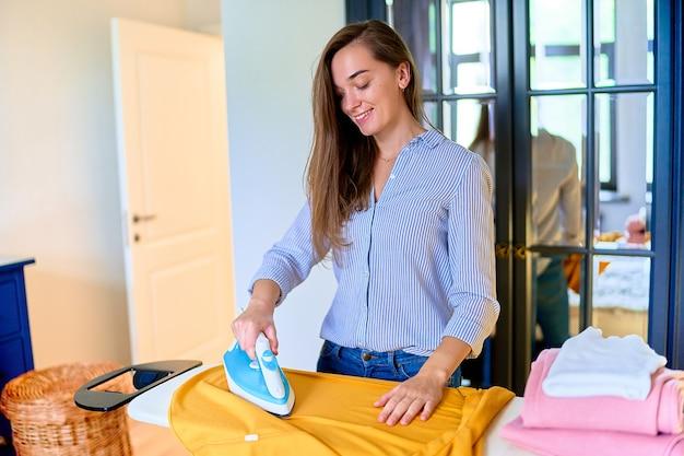 Sorrindo feliz linda fofa satisfeita moderna adulta jovem passando roupas lavadas na tábua de engomar em casa. tarefas domésticas