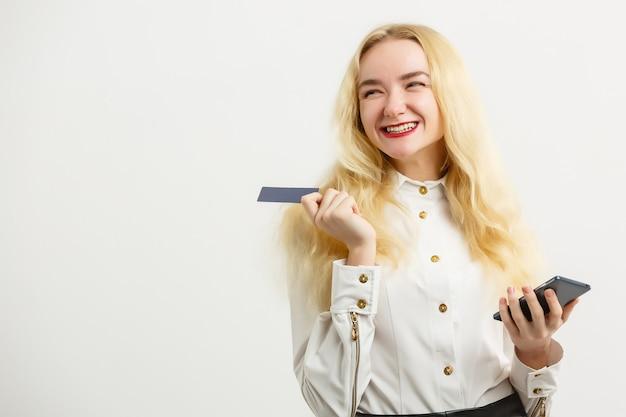 Sorrindo feliz mulher segurando o cartão de crédito e o celular enquanto olha para a câmera