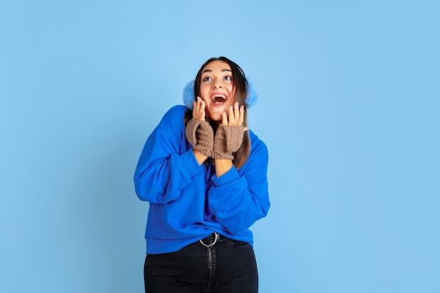 Sorrindo feliz. retrato de uma mulher caucasiana sobre fundo azul do estúdio. linda modelo feminino com roupas quentes. conceito de emoções, expressão facial, vendas, anúncio. clima de inverno, época de natal, feriados.