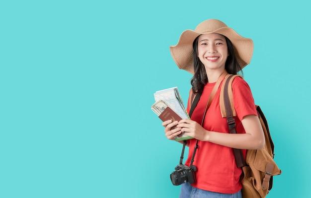 Sorrindo felizmente viajante asiático mulher segurando o passaporte com bilhete e mapa, dinheiro em azul.