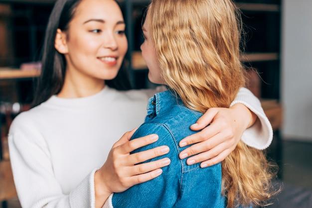 Sorrindo fêmeas abraçando em casa
