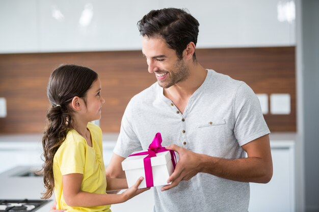 Sorrindo filha dando caixa de presente para o pai